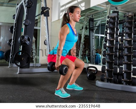 dumbbell squat woman workout exercise at gym - stock photo