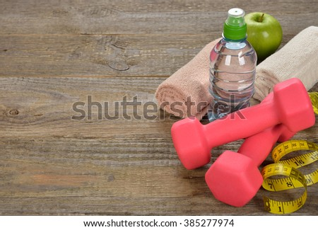 Dumbbell, water and towel on wooden background, fitness concept - stock photo