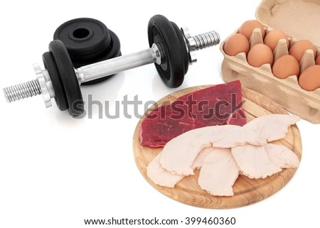 Dumbbell weights with high protein body building health food of chicken, lean steak and eggs. - stock photo