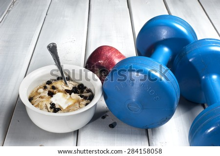 Dumbbells and red apple next to bowl with yogurt, muesli and honey on floor - stock photo