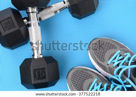 dumbbells and shoes on gym mat fitness concept - stock photo