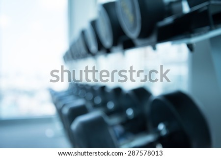 Dumbbells in modern fitness center abstract blur background