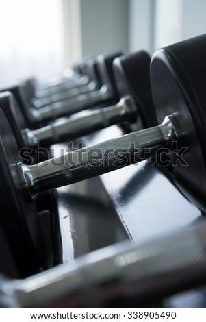 Dumbbells in modern gym fitness training center - Selective focus - stock photo
