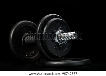 dumbbells on a black background - stock photo