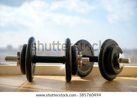 Dumbbells on the background of windows and the big city and sky.