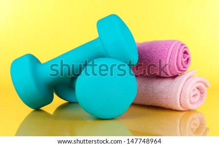 Dumbbells on yellow background - stock photo