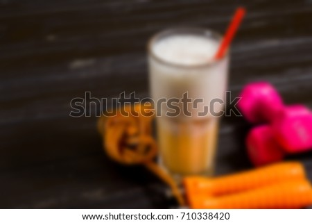 Dumbbells, skipping rope and protein blurred abstract background