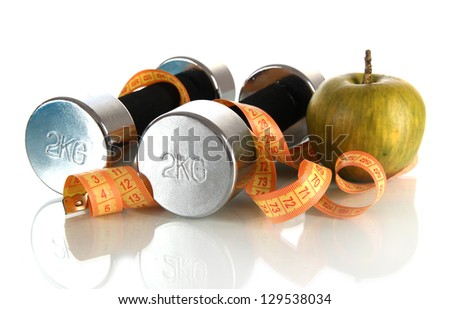 Dumbbells with apple and centimeter isolated on white - stock photo