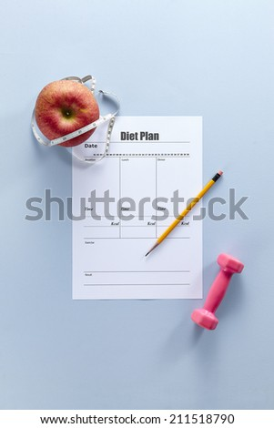 Dumbbells with measuring tape and diet Plan - stock photo
