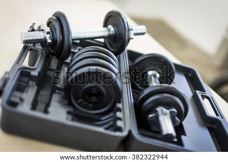 Dumbbells with weights on a workout bench.