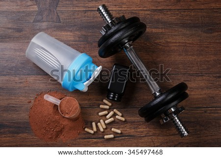 Dumbells and food supplements on the table