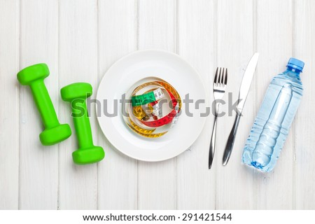 Dumbells and healthy food over wooden background. View from above - stock photo