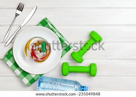 Dumbells and healthy food over wooden background. View from above with copy space - stock photo
