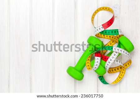 Dumbells and tape measure over wooden background with copy space. Fitness and health - stock photo