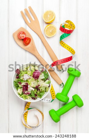 Dumbells, tape measure and healthy food. Fitness and health. View from above over wooden table - stock photo