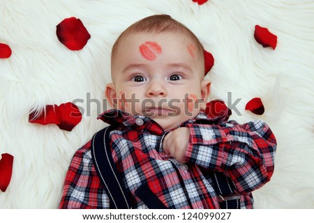 dumbfounded cute baby boy with lipstick and rose petals.