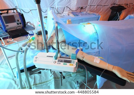 Dummy patient with an open abdomen on the operating table in modular tent - stock photo