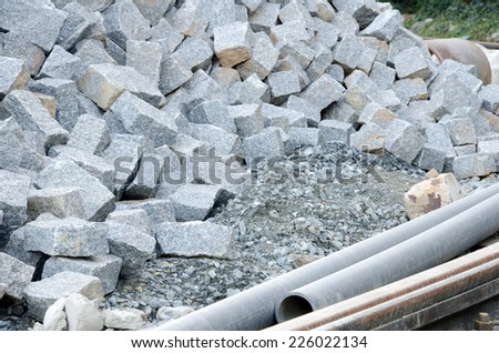 Dump of paving stones and several pipes in the front.  - stock photo