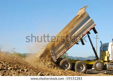 Dump truck dumping rock and dirt in the prep for a new business construction