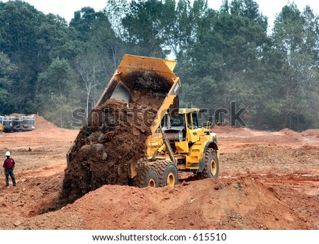 Dump Truck emptying its load - stock photo