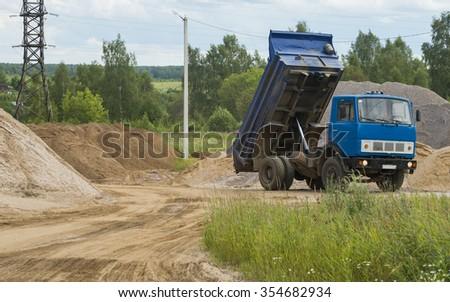 Dump truck unloads construction sand - stock photo