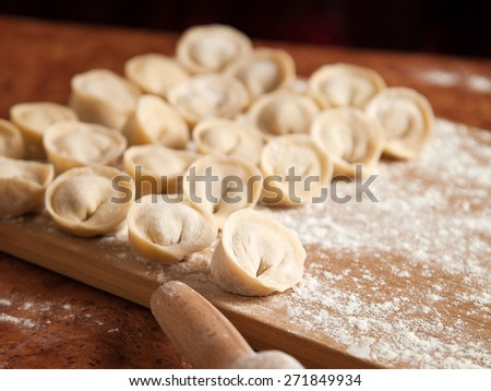 Dumplings and parsley - russian pelmeni. Cook dumplings. Pasta ravioli over wooden desk