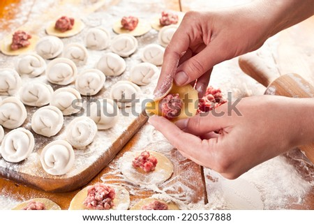 Dumplings. Dough with meat filling on the cook's hands. - stock photo