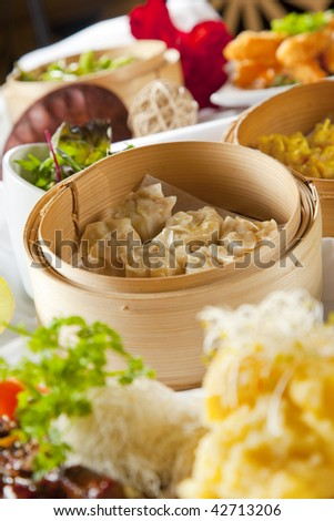 dumplings in bamboo steamer on dressed table with assortment of asian dishes - stock photo