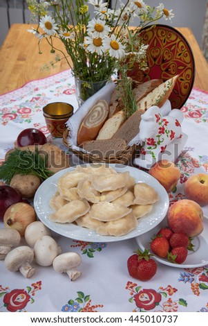 dumplings on a plate surrounded by assorted mushrooms and berries on table
