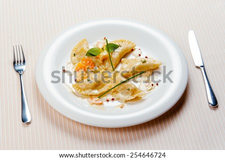 Dumplings on a white plate with knife and fork - stock photo
