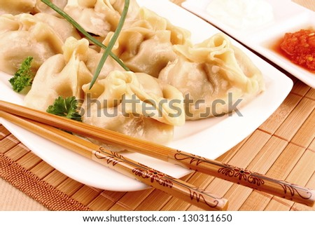 Dumplings on white plate with chopsticks and chilli sauce closeup - stock photo