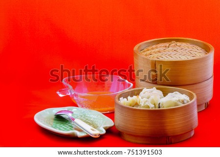Dumplings served in bamboo containers with chili sauce, red background captured high angle/Dumplings in bamboo containers/Dumplings served in bamboo containers with chili sauce in red background