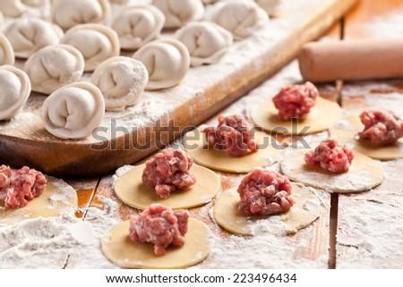 Dumplings. Uncooked on the wooden desk. - stock photo