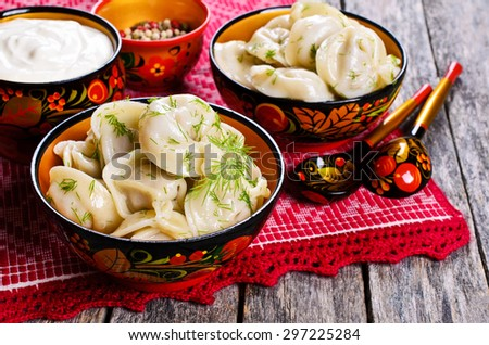 Dumplings with dill in a wooden plate in rustic style - stock photo