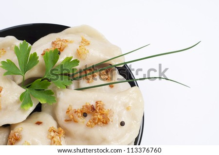 Dumplings with fried onion and herbs served an a plate. - stock photo
