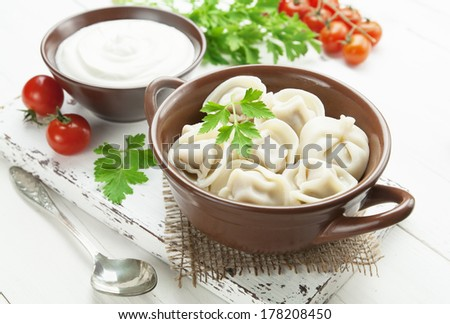 Dumplings with meat  and sour cream Pelmeni russian national dish - stock photo