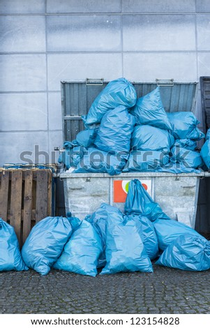 dumpster filled with blue garbage bags - stock photo