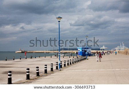 DUN LAOGHAIRE, IRELAND - August 15: Unidentified people walk along Dun Laoghaire's East pier on August 15, 2015 in Dun Laoghaire, Ireland.