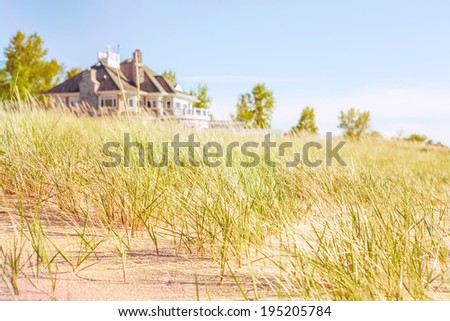 Dune grasses with beach house  - stock photo