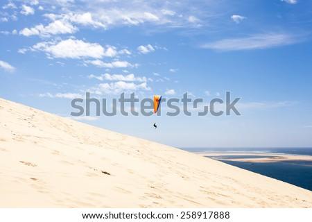 Dune of Pyla paragliding - stock photo
