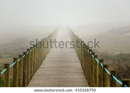 Dune wooden walkway towards the beach, in a foggy late summer afternoon. North of Portugal. - stock photo