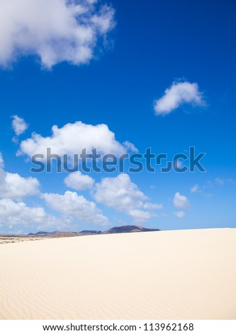 dunes abstract - bright sunshine showing wind patterns on sand, volcano Bayuyo on the distance - stock photo