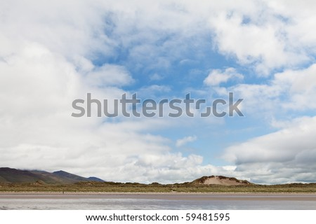 Dunes blue sky with white clouds and sandy beach at Dingle Peninsula Ireland nice background with copy space - stock photo