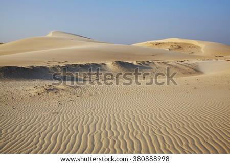 Dunes, rippled sand going far under blue sky, Vietnam - stock photo