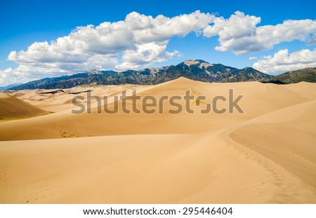 Dunes with Fluffy Clouds at Great Sand Dunes National Park - stock photo