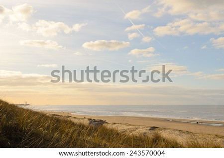 Dunes with some grass, sand beach and North sea at the west coast of Holland during a summer evening. - stock photo
