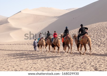 DUNHUANG,CHINA-OCTOBER 16: A group of camels walking in the Mingsha sand dunes mountain on October 16, 2013 in Dunhuang, China. - stock photo