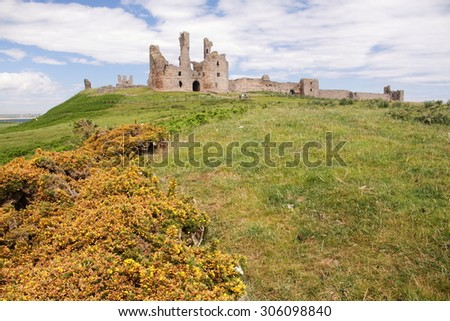 dunstanburgh castle ruins of the old medieval fortress northumberland england - stock photo