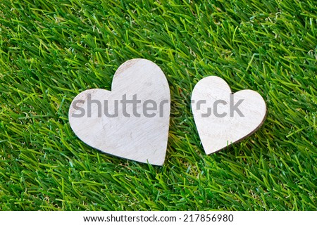 Duo of hearts in different sizes on green grass symbolic of love and romance for a Valentines Day, special occasion anniversary - stock photo