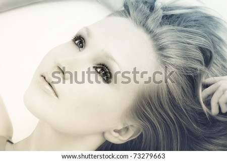 Duotone colored portrait of young beautiful woman with long fair hair lying on white background and looking upwards